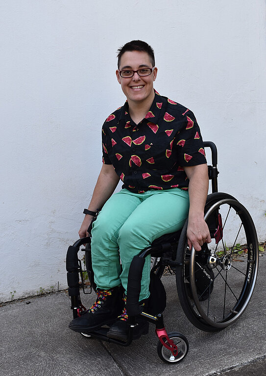 Jax is a white, mid 30's manual wheelchair user. They sit in their black and red wheelchair wearing a black shirt with red watermelons on it. They have on red glasses, short dark brown hair, pale green jeans, and black boots with rainbow laces. They are smiling at the camera.